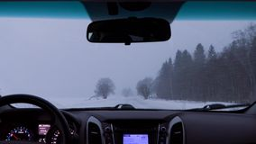 Driving a car on a winter country road during a snow storm stock footage