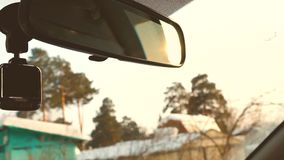 Driving car in winter countryside in slow motion. Sunset sun in rear view mirror. Inside car view stock video