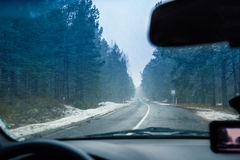 Driving a car on winter road in blizzard Stock Images