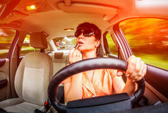 Driving a car. Women make up lips at the wheel the car, not stares on the road creating an emergency situation Royalty Free Stock Photos