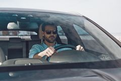 Driving carefully. Handsome young man looking straight while driving a status car royalty free stock image
