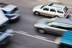 Driving cars in city traffic. Driving cars on a city street, in motion blur Royalty Free Stock Images