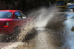 Driving cars on a flooded road during floods caused by rain storms. Cars float on water, flooding streets. Splash on the machine. Flooded city road with a big royalty free stock photo