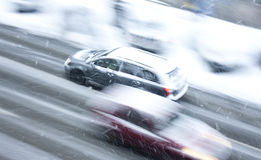 Driving cars on the snowy city street Stock Photos