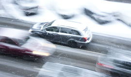 Driving cars on the snowy city street in motion blur Royalty Free Stock Photos