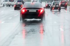 Driving cars on a wet street with splashing water in motion blur Stock Photo