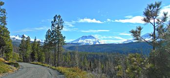 Driving in the Cascades. View along FR 1514 of the Three Sisters and Broken Top in the Cascade Range - near Sisters, OR stock image