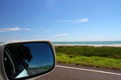 Driving the coast. Unspoilt coastal views and the open road reflected in a car rear view mirror Stock Photography