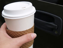 Driving with coffee. Hand holding a disposable coffee cup outside of a car Royalty Free Stock Photography