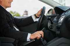 Driving with comfort. Close-up of cheerful mature man in formalwear driving car and smiling Stock Photography