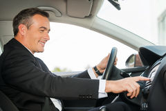 Driving with comfort. Side view of cheerful mature man in formalwear driving car and touching dashboard with finger Stock Image