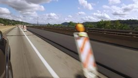Driving Through a Road Work Zone with Highway Cones. Driving through a construction zone on a highway next to a closed lane marked with orange cones and barriers stock video