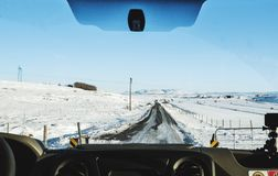 Driving on the country road in winter. Looking through car front windscreen, frozen road with snow covered and clear blue sky in I Stock Photos