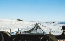 Driving on the country road in winter. Looking through car front windscreen, frozen road with snow covered and clear blue sky in I Stock Photo