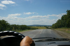 Driving in the countryside. Blurred hand of driver on steering wheel driving on countryside highway and blue sky with white clouds Stock Photos