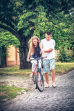 Driving of a couple by bicycle down street cities royalty free stock photos