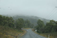 Driving on curve winding  Arthur Road, Tasmania. Cloud filled Way from Boomer Island and Boomer bay on Arthur Highway on way to Port Arthur, Hobart, Australia Stock Image