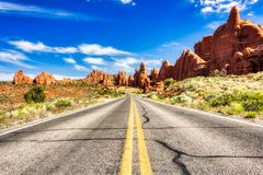 Driving through the-Desert with Monument Rock along the Road During Sunny Day, Arches NP. USA stock image