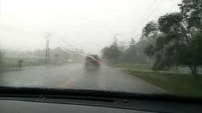 Driving down country road on a rainy day. Looking thru the windshield on a rainy day. There is a car in front with its red tail lights glowing and green trees Stock Images