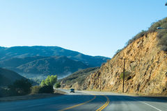 Driving down foggy highway in Malibu Creek State Park. With mountains in background Stock Images