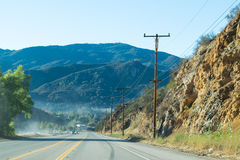 Driving down foggy highway in Malibu Creek State Park. With mountains in background Stock Photos