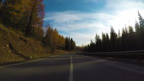 Driving down a quiet rural highway during the day in autumn.