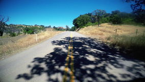 Driving down tree lined Rural Road POV. POV of driving down rural road stock footage