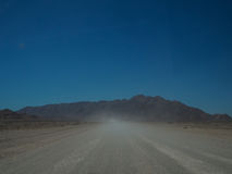 Driving through dusty unpaved road to rocky mountain among deser Stock Images