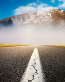 Driving on an empty asphalt road at the misty mountains Royalty Free Stock Images