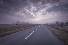 Driving on empty asphalt road at misty sunrise. Open straight road in Deliblato Sands at foggy morning Stock Images