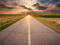 Driving on an empty asphalt road at sunset Stock Images