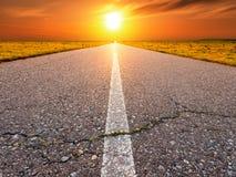 Driving on an empty asphalt road towards the sun Royalty Free Stock Photo