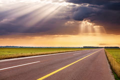 Driving on empty highway towards the sunbeams Stock Photography