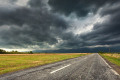 Driving on an empty old road at stormy weather Royalty Free Stock Photography