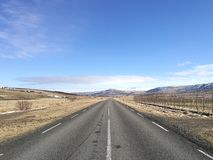 Driving on empty open asphalt road towards range of mountains covered in snow on blue sky sunny day, business success and way forw Stock Photos