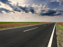 Driving on an empty open road at idyllic sunny day Stock Photos