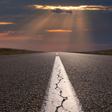 Driving on empty open road towards the setting sun Stock Photography