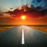 Driving on an empty road against the setting sun Royalty Free Stock Image