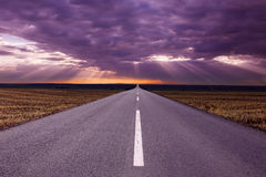 Driving on an empty road at beautiful sunrise. Asphalt road in the fields before the storm Royalty Free Stock Images