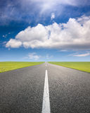 Driving on an empty road through the fields Royalty Free Stock Photo