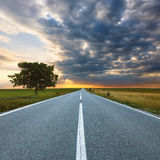 Driving on an empty road at sunrise Stock Image