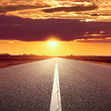 Driving on an empty road at sunset Stock Image