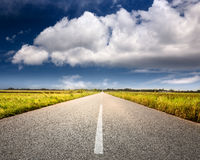 Driving on an empty road towards the big cloud Royalty Free Stock Image