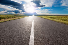 Driving on empty road towards the sun Royalty Free Stock Photo