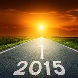 Driving on an empty road towards the sun to 2015 Stock Photos
