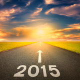 Driving on an empty road towards the sun to 2015 Royalty Free Stock Photo