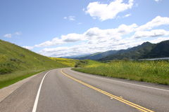 Driving for ever. Pretty back road in the spring time, lake and blue skies and clouds stock photos