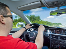Driving experience... An inside, rear seat, wide-angle view of a casual dressed man in his forties driving a car Royalty Free Stock Photo