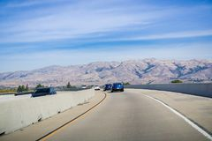 Driving on the express lane to switch between highways. Mission peak, Monument peak and Allison peak in the background; Milpitas, south San Francisco bay stock photography