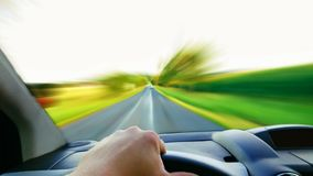 Driving a fast car POV. First person view of the driver behind the wheel. Driving a fast car with high speed blurred front road stock photos